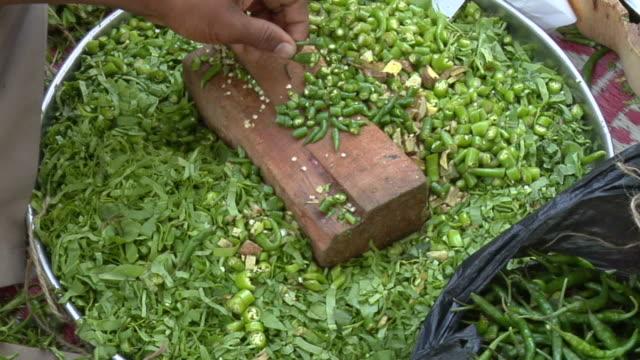CU, Man's hands cutting spinach and green chilies, Mumbai, Maharashtra, India