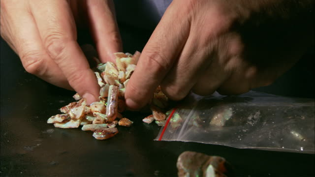 cu man's hands examining small opal chunks, coober pedy, south australia, australia - coober pedy stock videos & royalty-free footage