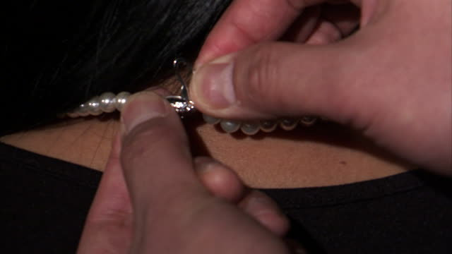 ecu man's hands fastening pearl necklace around woman's neck / orem, utah, usa - 人の首点の映像素材/bロール