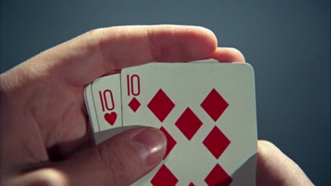 1966 cu man's hands holding cards, playing stud poker - poker stock-videos und b-roll-filmmaterial