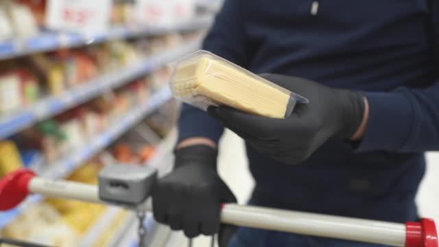 vídeos de stock, filmes e b-roll de mãos de homem em luvas de proteção segurando queijo em uma loja de compras - cheese