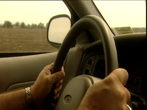 Man's hands on steering wheel of car driving in rural area Iowa
