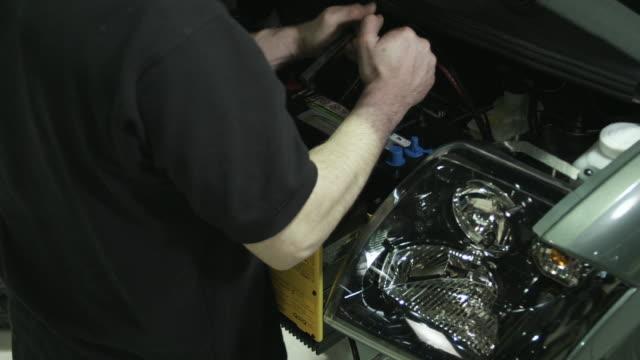 cu man's hands placing battery into front of electric car on assembly line, st. jerome, quebec, canada - batteri bildbanksvideor och videomaterial från bakom kulisserna