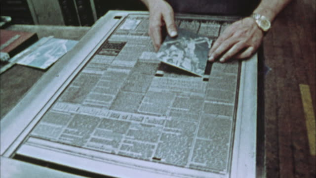 cu, man's hands placing photo in newspaper page form, 1970's, los angeles, california, usa - newspaper page stock videos and b-roll footage
