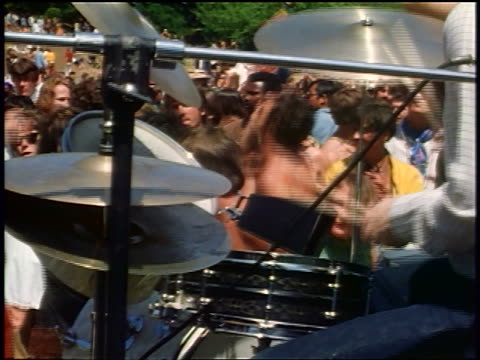 vídeos de stock e filmes b-roll de 1968 man's hands playing drums with dancing audience in background / tilt up to back of singer / ca / newsreel - love in