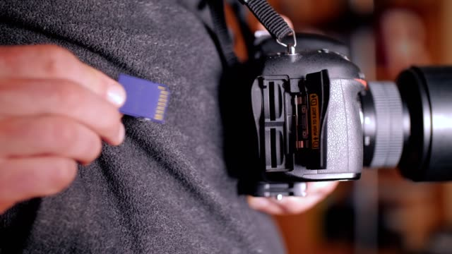 a man's hands plugging in the sd card to his dslr camera, mirrorless camera, photography and cinematography use, videography equipment - electrical equipment stock videos & royalty-free footage