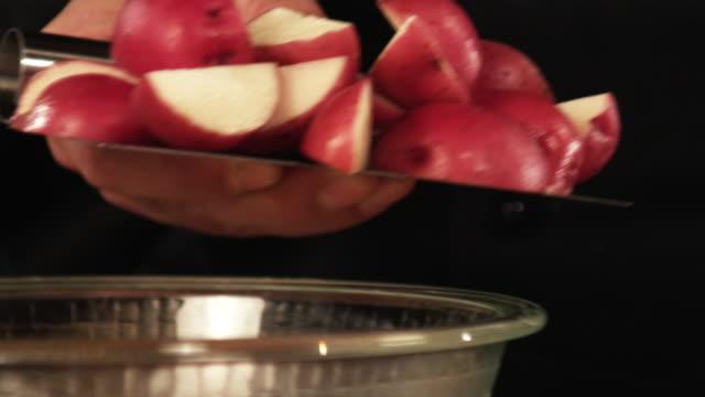 vidéos et rushes de slo mo, ecu, man's hands pouring sliced potatoes to bowl - pomme de terre rouge