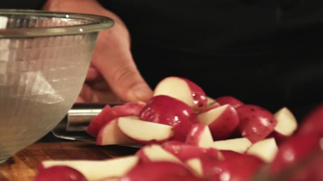 vidéos et rushes de slo mo, ecu, selective focus, man's hands pouring sliced potatoes to bowl - pomme de terre rouge
