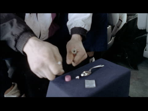 stockvideo's en b-roll-footage met / cu man's hands preparing cocaine injection in spoon preparing syringe and injecting drug into his arm man shooting up drugs on january 01 1996 in... - injecting heroin