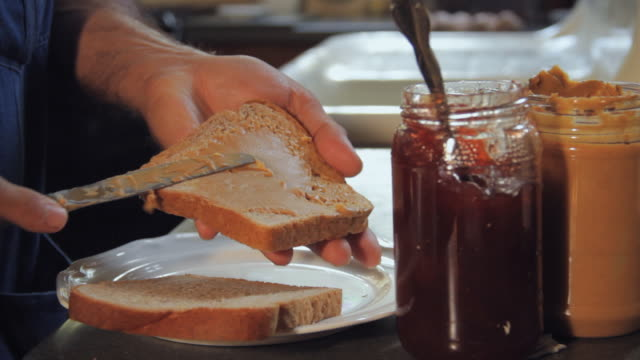 cu man's hands preparing sandwich with peanut butter and jelly / madison, florida, usa - making a sandwich stock videos and b-roll footage