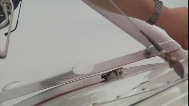 vidéos et rushes de a man's hands pump fuel into a biplane. - faire le plein d'essence