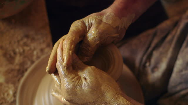 man's hands shape clay on potter's wheel - プレイドシャツ点の映像素材/bロール