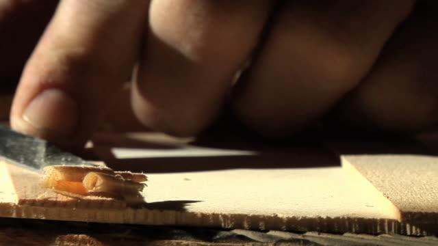 SLO MO ECU FOCUSING Man's hands shaping piece of wood