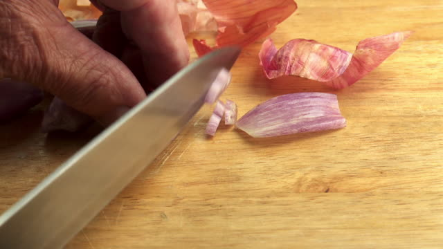 man's hands slicing shallot with sharp kitchen knife, - shallot stock videos & royalty-free footage