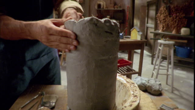 A man's hands smooth and shape a cylinder of clay.