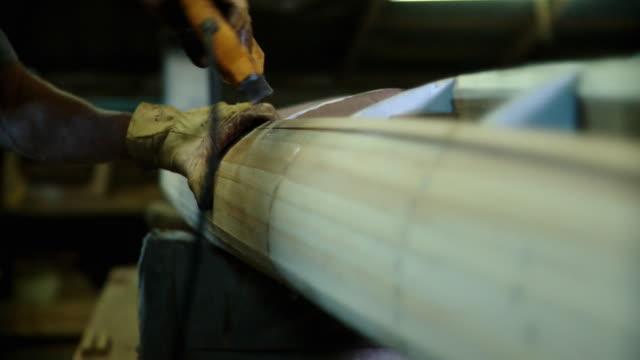CU SELECTIVE FOCUS, Man's hands stapling wood strips into kayak in workshop, Live Oak, Florida, USA