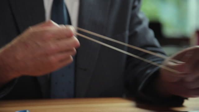 vidéos et rushes de cu man's hands stretching rubber-band at desk / portland, oregon, usa - souplesse