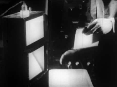 stockvideo's en b-roll-footage met b/w 1924 man's hands takes film from cylinder puts it in developer / photo sent by wire / newsreel - 1924