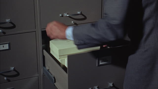 1967 CU ZI Man's hands taking files from large metal file cabinet