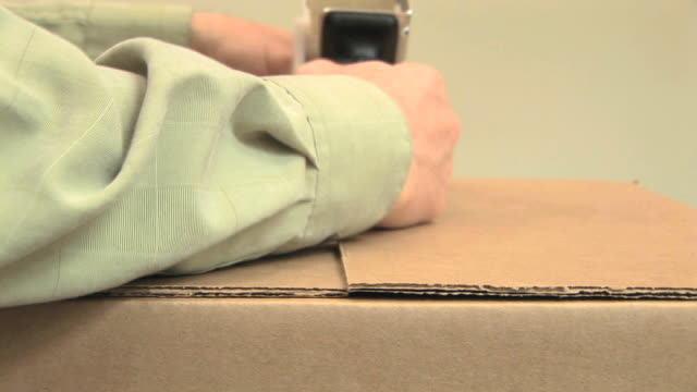 ECU SELECTIVE FOCUS Man's hands taping up cardboard box with tape dispenser, Brush Prairie, Washington, USA