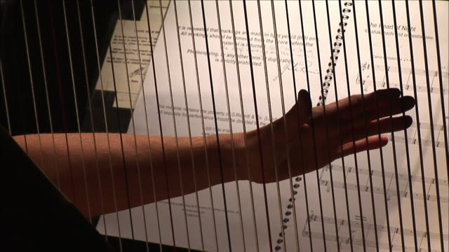 CU Man's hands  touching harp strings, sheet music in background, Melbourne, Victoria, Australia