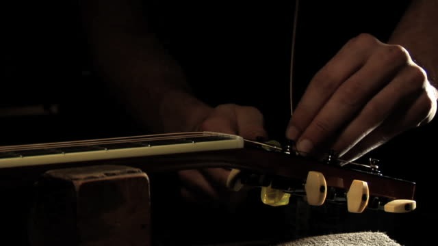 SLO MO CU Man's hands turning tuning peg of acoustic guitar
