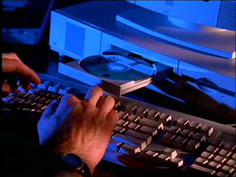 man's hands typing on computer / zoom in to cd-rom - cd rom stock videos & royalty-free footage