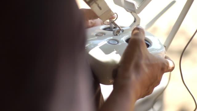 mani dell'uomo che usa un telecomando per guidare il drone - remote control video stock e b–roll