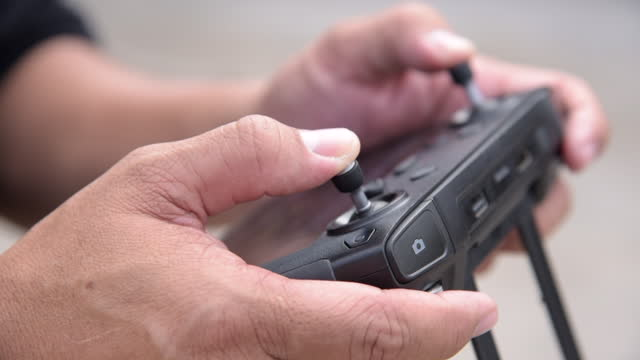 stockvideo's en b-roll-footage met de handen van de mens gebruikend een afstandsbediening met monitor om de drone te drijven - control