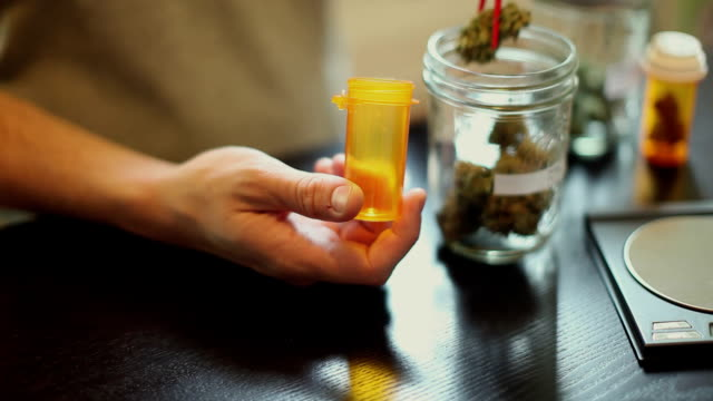 CU SELECTIVE FOCUS Man's hands using chop sticks to remove medicinal marijuana from mason jar and placing it in prescription bottle / Simi Valley, California, USA