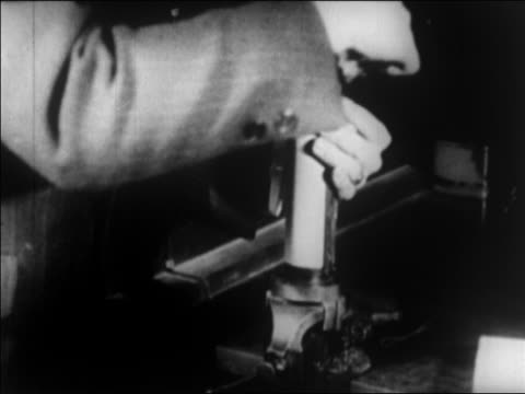 vidéos et rushes de b/w 1924 man's hands wrap photograph around cylinder to send photo by wire / newsreel - 1924