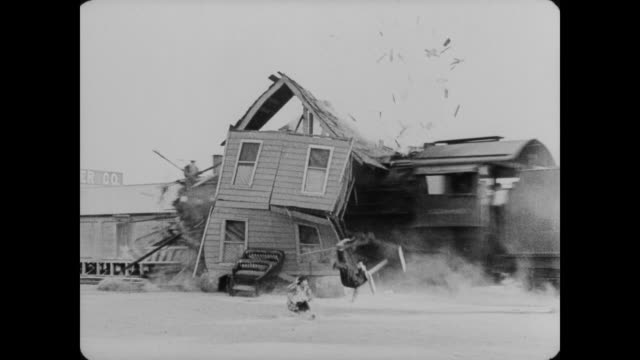 1920 man's (buster keaton) house is hit by a train when it gets stuck on train tracks - loss stock videos & royalty-free footage