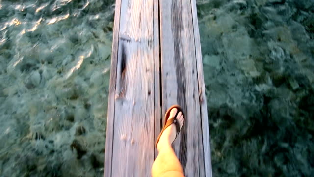POV of mans legs and feet walking on wooden dock over water at sunrise.