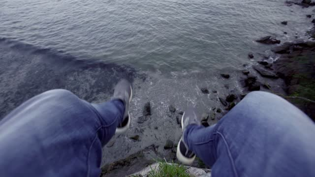 vídeos de stock e filmes b-roll de man's legs dangling during break on a cliff, galicia, spain - jeans