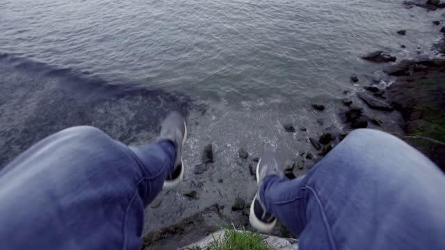 vídeos de stock e filmes b-roll de man's legs dangling during break on a cliff, galicia, spain - calças de ganga