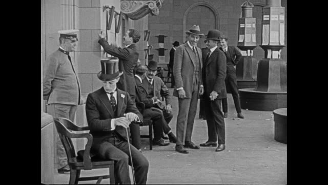 1920 man's (buster keaton) misunderstanding at the stock exchange becomes entertainment for others - buster keaton stock videos and b-roll footage