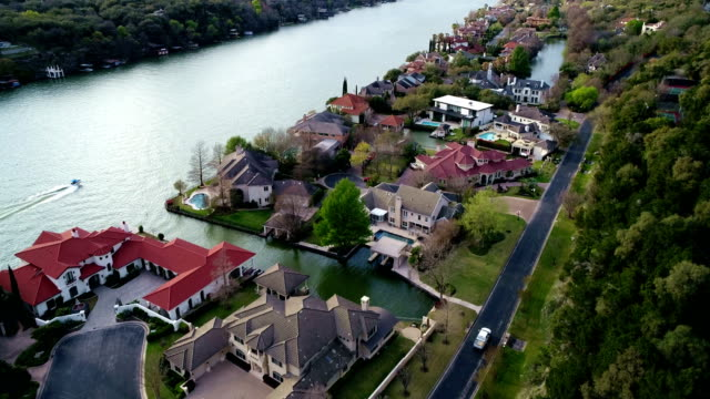 vídeos de stock e filmes b-roll de mansions along riverside with boats and recreation on town lake - town
