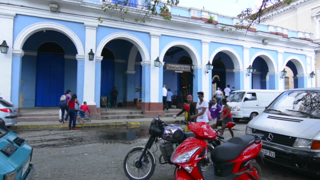 Mantanzas Cuba traffic and rush outside Ediciones Vigia bookstore with blue building in downtown center