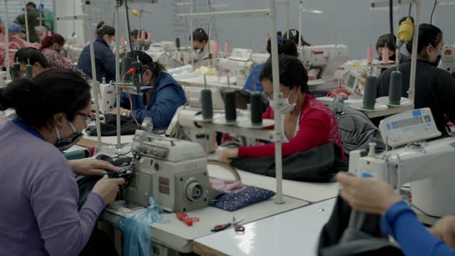 manual female workers working at their sewing station in a textile factory all wearing protective face masks - textile stock videos & royalty-free footage