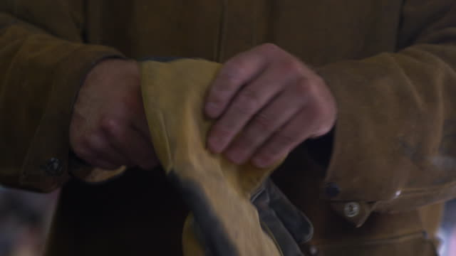 Manual laborer takes off his protective gloves to reveal his hard working hands