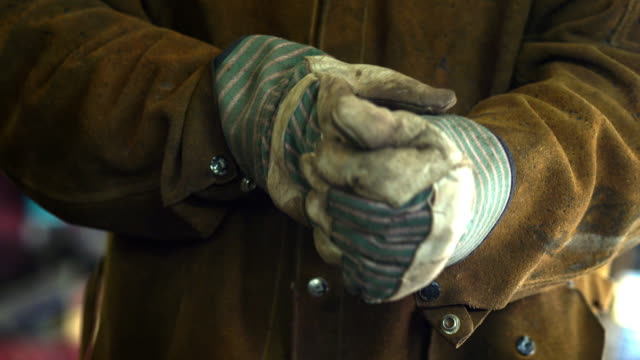 manual laborer takes off his protective gloves to reveal his hard working hands - schutzhandschuh stock-videos und b-roll-filmmaterial