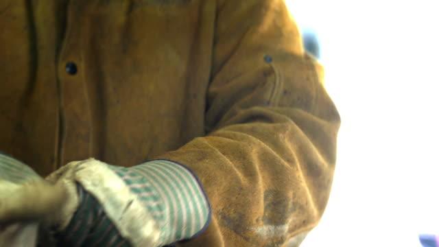 vídeos y material grabado en eventos de stock de manual laborer takes off his protective gloves to reveal his hard working hands - guantes de protección