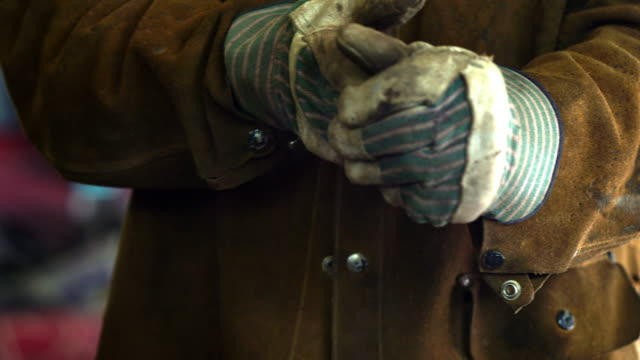 vídeos de stock, filmes e b-roll de manual laborer takes off his protective gloves to reveal his hard working hands - luvas