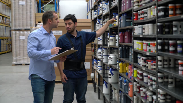 Manual worker and administrator of a storehouse doing a checklist of materials on shelves