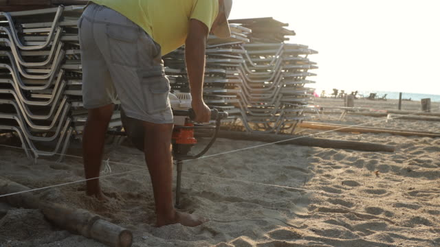 manual worker digging hole to place beach umbrella - bending over stock videos & royalty-free footage