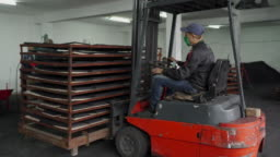 Manual worker driving electric forklift in warehouse of factory for coconut charcoal for hookah