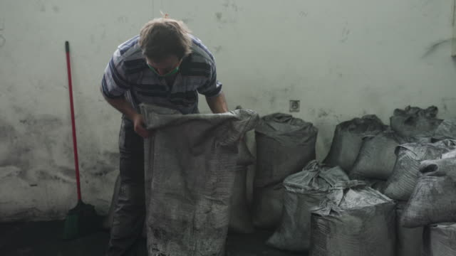 manual worker emptying sack full of coconut charcoal for hookah in warehouse of factory - sack stock videos & royalty-free footage