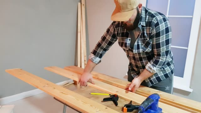 manual worker hands working with a measuring tape and pencil in wood plank - timber stock videos & royalty-free footage