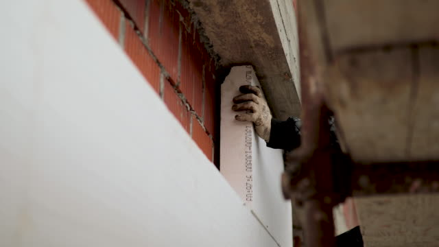 manual worker in bib bib overalls installing rigid styrofoam insulation board for energy saving on exterior wall of building - bib overalls stock videos & royalty-free footage