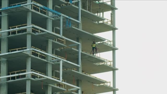 manual worker inside a newly constructed industrial site - beton stock-videos und b-roll-filmmaterial